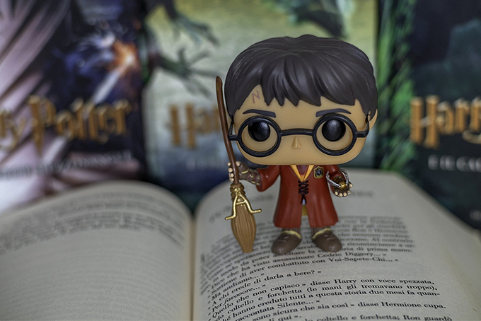 Photo représentant une figurine de Harry Potter, balai à la main debout sur un livre ouvert