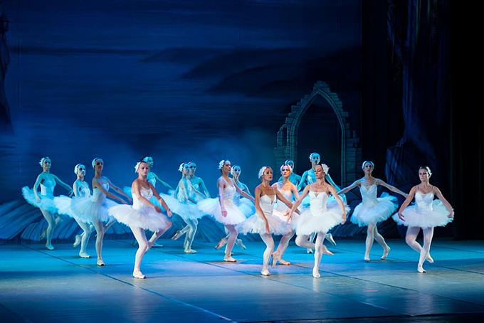 Dans une lumière bleutée, photo représentant plusieurs danseuses de ballets en train de danser.