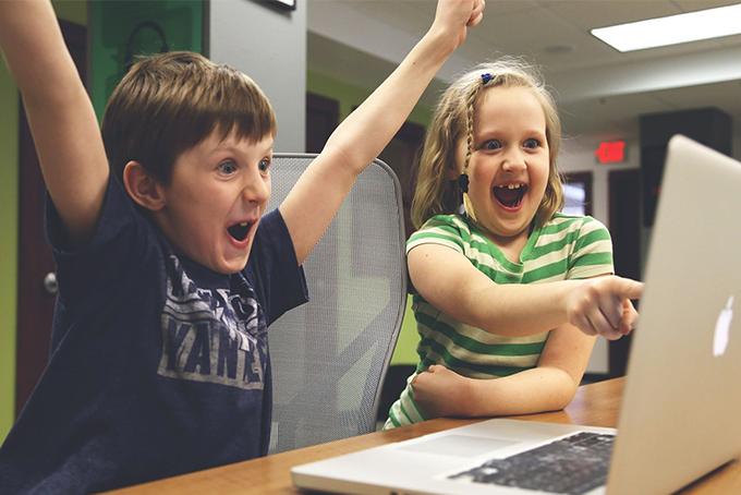 Photo représentant deux enfants devant un ordinateur. Le petit garçon a les bras en l'air et il ets très joyeux. La petite fille à ses côtés pointe l'ordinateur du doigt