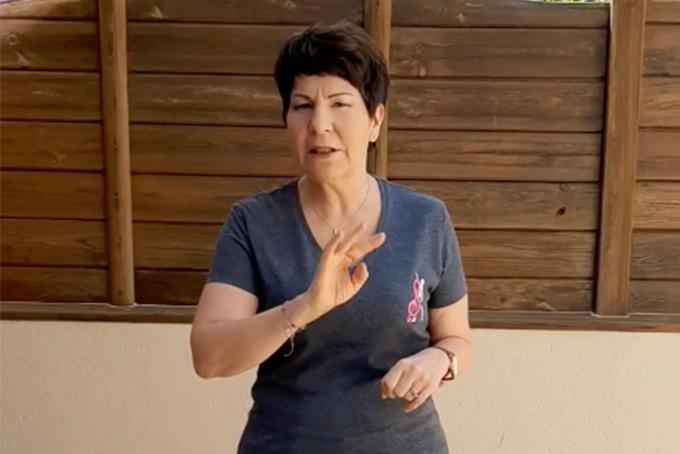 Photo représentant une femme un bras en avant en train de parler.