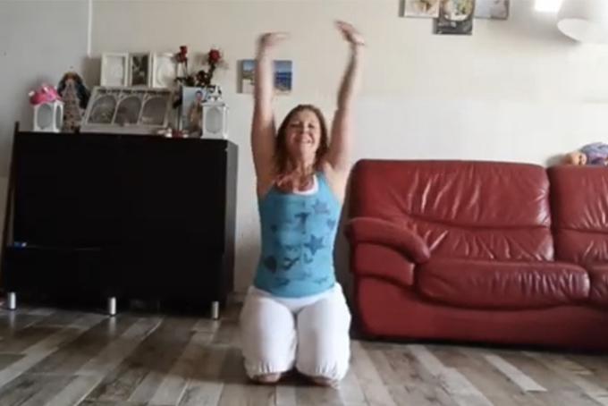 Photo représentant une jeune femme en train de danser. Elle est agenouillée et lève les bras en l'air.