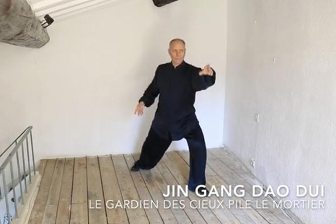 Photo représentant un homme vêtu de noir en pleine séance de Tajii Quan. Il effectue des mouvements lents. En appui sur sa jambe gauche, il tend son bras gauche vers l'avant et le bras droit vers l'arrière.