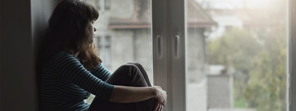 Photo d'une femme isolée regardant tristement l'extérieur de sa fenêtre