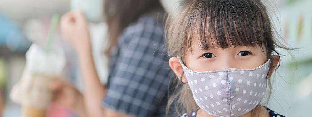 Photo d'une petite fille portant un masque