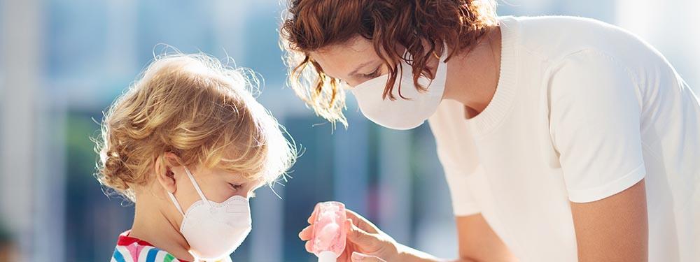 Photo d'une maman avec son fils en train de lui mettre du gel hydro alcoolique sur les mains