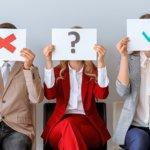 Photo de 5 personnes hommes et femmes assis sur une chaise avec des pancartes devant le visage : point d'interrogation, croix rouge, check vert