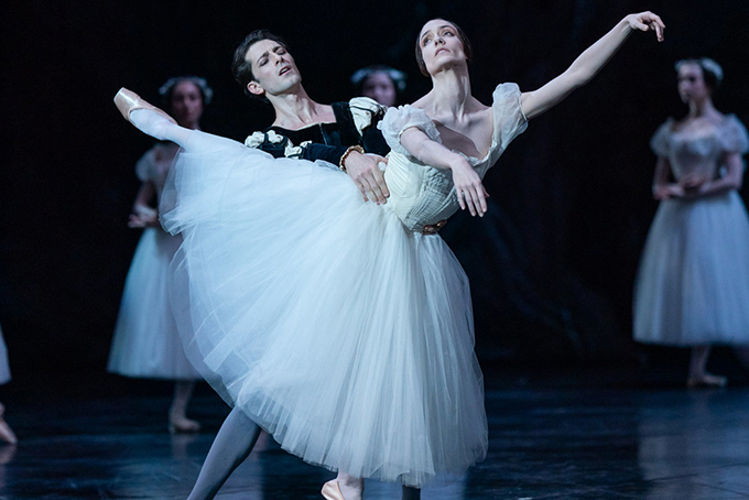 Photo représentant deux danseurs de ballet. Une danseuse vêtue d'un tutu blanc danse avec un homme. Soutenu par le danseur, la femme s'élance un bras tendu vers le ciel et une jambe en l'air.