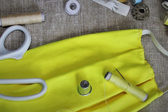 Photo représentant un masque en tissu jaune. Il est posé sur une table. On aperçoit près du masque des ciseaux de couture, du fil et des aiguilles.
