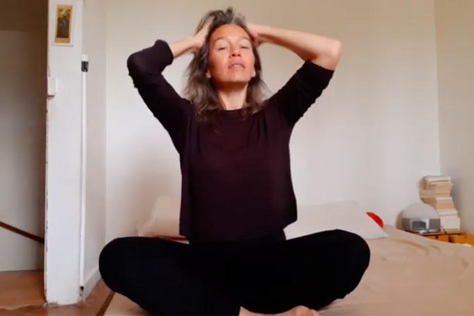 Photo représentant une femme assise en tailleur. Elle est en train de se masser le cuir chevelu énergiquement.