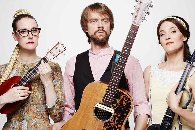 Photo représentant deux femmes et un homme barbu en train de poser avec leurs instruments de musique. L'homme porte une guitare, la femme à gauche un ukulélé et la femme à droite un violon.