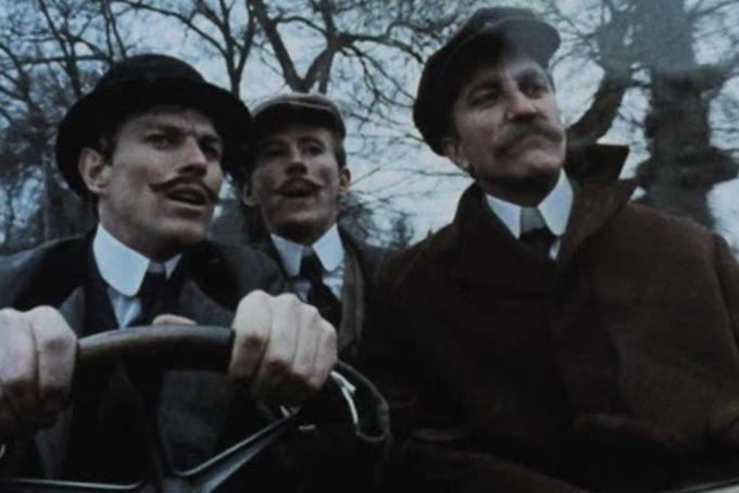 Photo représentant trois personnages des brigades du tigre à bord d'une voiture. Ils portent tous les trois une moustaches et un chapeau.