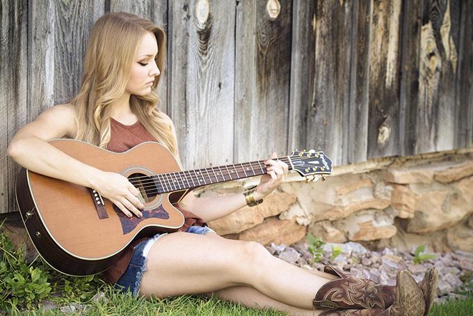 Photo représentant une femme blonde assise en train de jouer de la guitare
