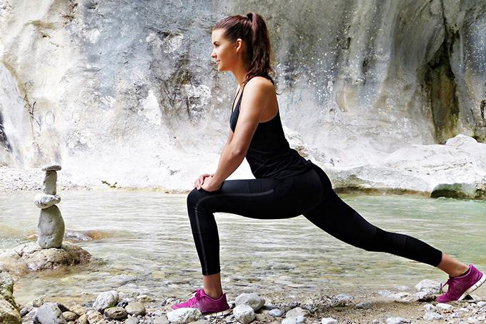 Photo représentant une femme en mouvement au bord d'une rivière. Elle est appuyée sur son genou et elle a une jambe tendue vers l'arrière.