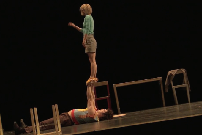 Photo représentant un homme et une femme sur scène. L'homme est allongé sur la scène et porte à bout de bras la femme qui se tient debout sur ses mains.