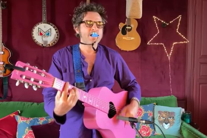 Photo représentant le chanteur M en train de chanter. Il est habillé en violet, joue d'une guitare rose et a un sifflet bleu dans la bouche. Il porte également des lunettes.