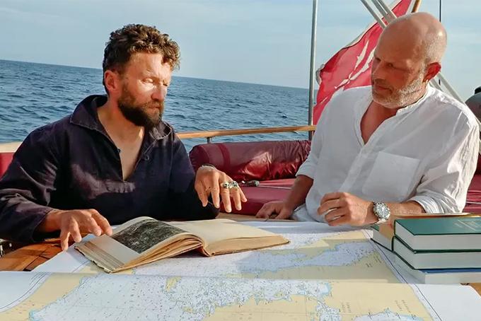 Photo représentant deux hommes sur un bateau en train de naviguer. Devant eux un livre ouvert, l'homme à gauche est en train de lire.