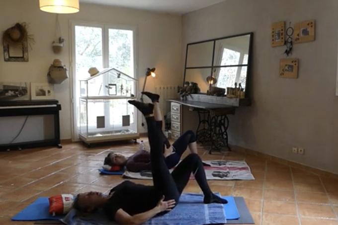 Photo représentant deux femmes allongées sur un tapis. Elles ont un genou replié et une jambe en l'air.