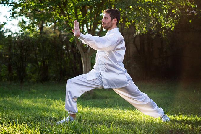 Photo représentant un homme en pleine nature. Il est habillé tout en blanc et il est en mouvement. Il est de profil, il est en appui sur sa jambe gauche et le bras tendu paume ouverte.