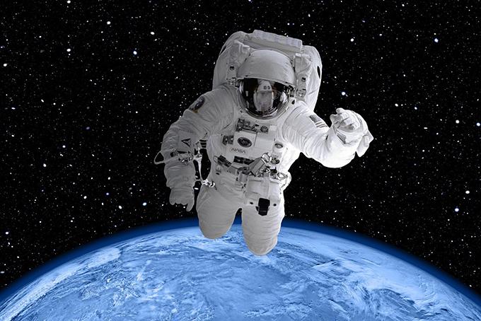 Photo représentant un cosmonaute dans l'espace. De loin, on distingue la terre.