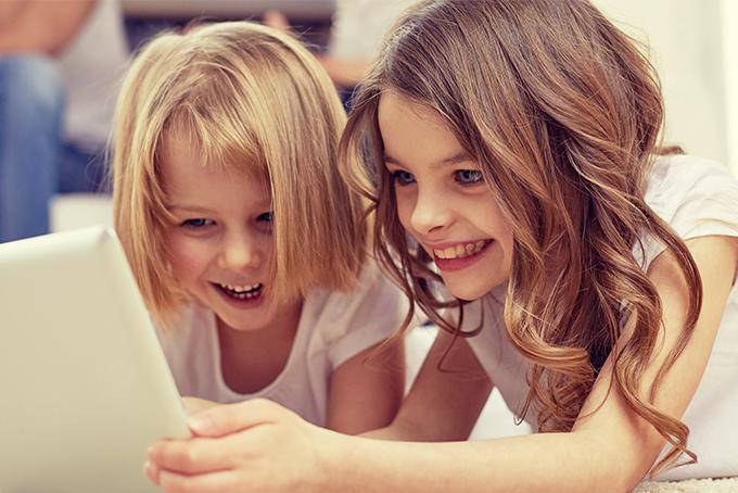 Photo représentant deux petite fille en train de rire en lisant une histoire sur une tablette.