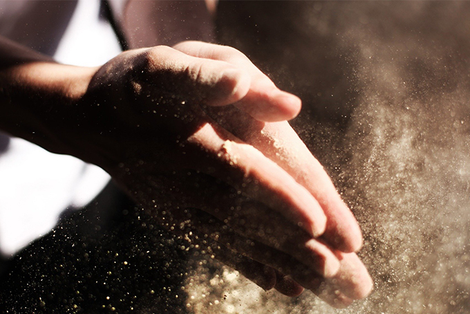 Photo représentant un gros plan sur des mains en train de taper l'une dans l'autre. On aperçoit la poussière dans la lumière.