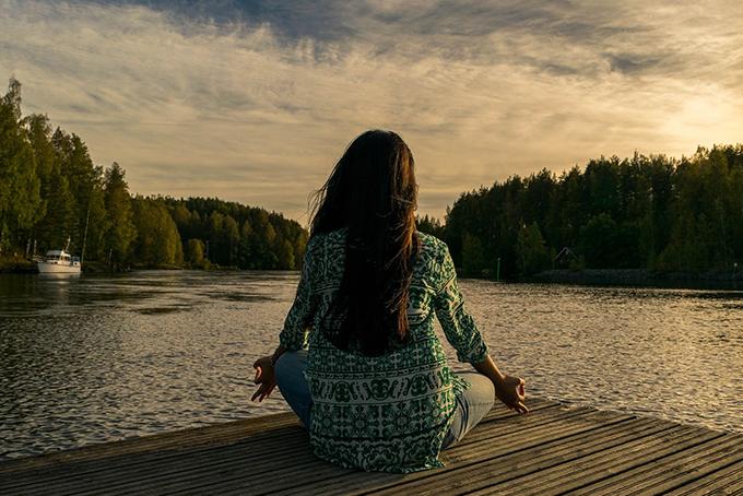 Photo représentant une femme en pleine nature, elle a les bras tendus en l'air et les yeux tournés vers le ciel.