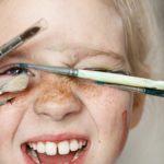 Photo du visage d'une petite fille couverte de peinture s'amusant à se cacher derrière des pinceaux
