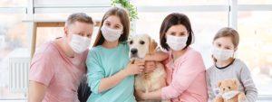 Photo d'une famille avec parents, 2 petites filles et 1 chien portant 1 masque
