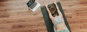 Photo d'une femme en position de yoga sur un tapis chez elle avec un ordi allumé montrant les exercices à reproduire