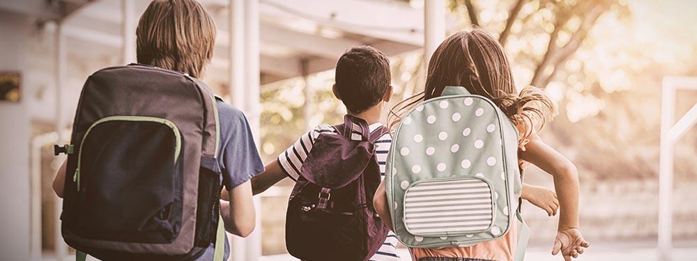 Photo de 3 élèves de dos avec leurs cartables dans une cours d'école en train de courir