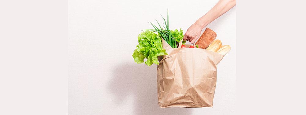Photo d'un sac de course rempli de légumes, pain… tenu par une main