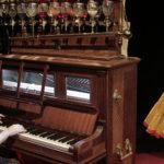 Photo d'une artiste sur scène en costume à côté d'un orgue