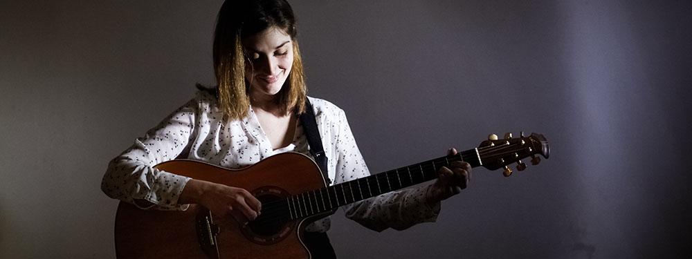 Photo de l'artiste Augustine Hoffmann en train de jouer de la guitare