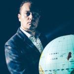 Photo de Bastien Lucas posant avec une map monde dans les mains