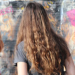 Photo représentant 3 adolescents en train de contempler une oeuvre de Street art. On y distingue plusieurs personnages en noir et blanc sur fond de jaune et rouge