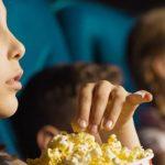 Photo d'une petite fille dans une salle de cinéma en train de manger des pop-corn