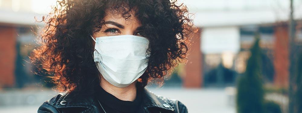 Femme posant avec un masque sur la bouche