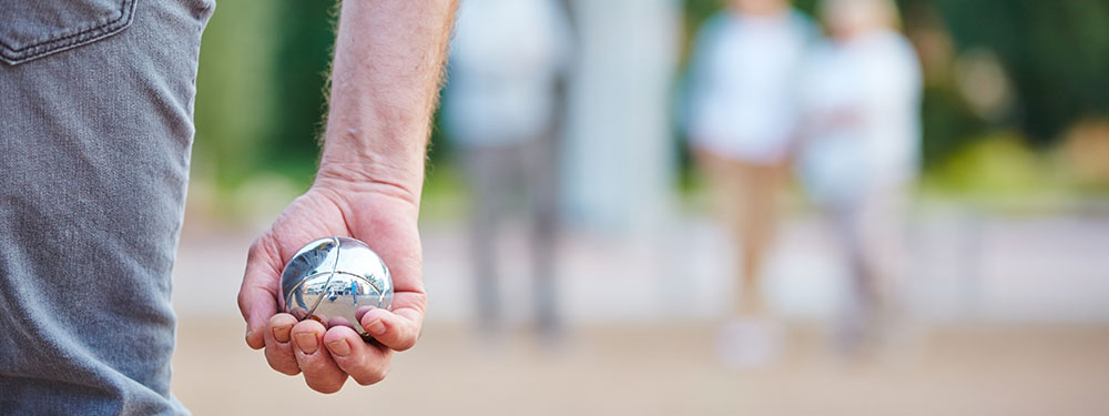 photo montrant un homme de dos, une boule de pétanque à la main, prêt à tirer