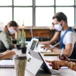 Photo de 4 personnes en trion de travailler sur une table respectant les mesures sanitaires