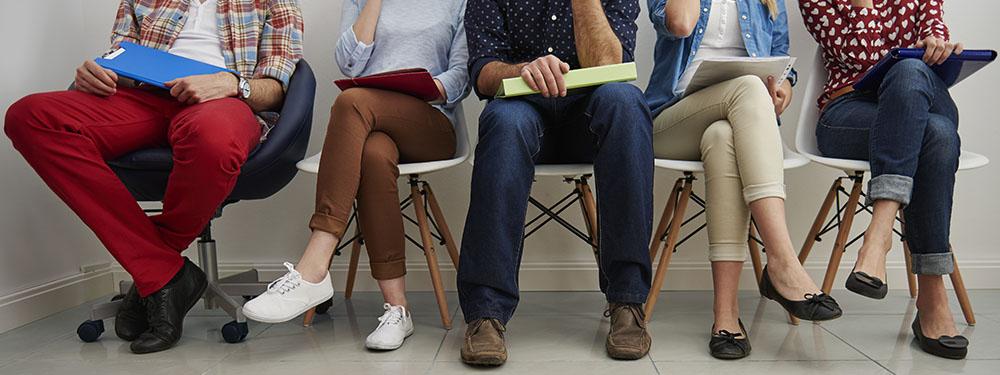 Photo montrant de jambes d'hommes et femmes assis sur des chaises attendant leur tour pour un recrutement