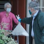 Photo d'un homme livrant un repas à domicile à une senior