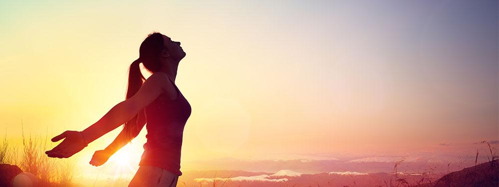 Photo d'une femme détendu respirant l'air des montagnes dans un soleil couchant