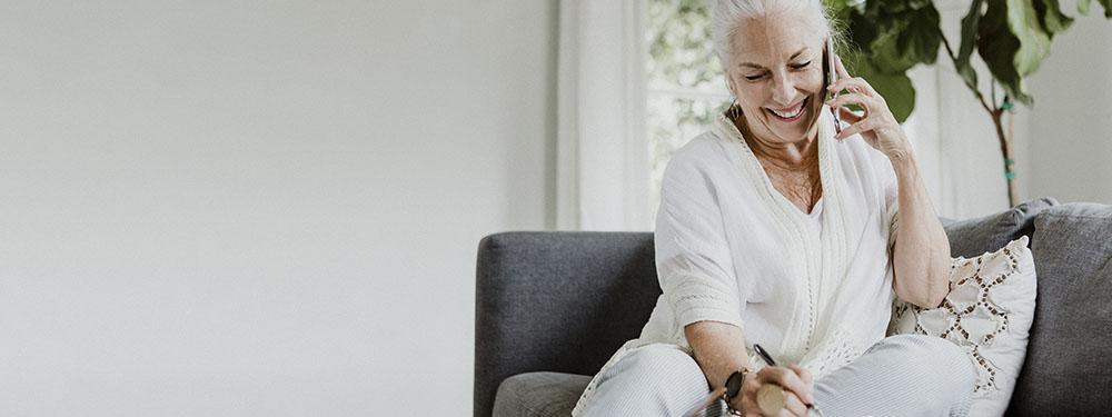 Photo d'une femme senior installée sur son canapé au téléphone en train de prendre RDV