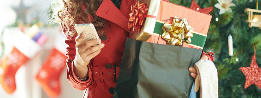 Photo d'une femme portant des cadeaux de Noel dans les bras