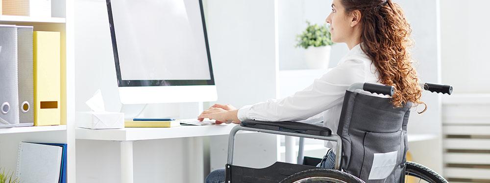 Photo d'une femme en fauteuil roulant assise devant un ordinateur