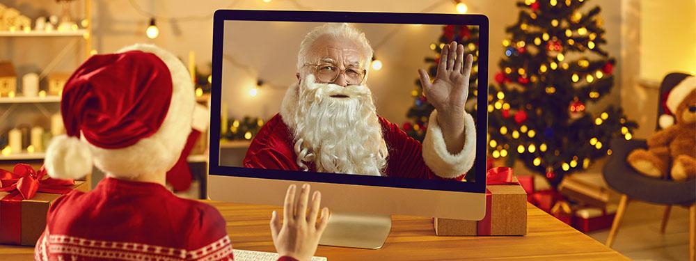 Photo d'un père Noel en Visio sur ordinateur faisant coucou à un enfant chez lui