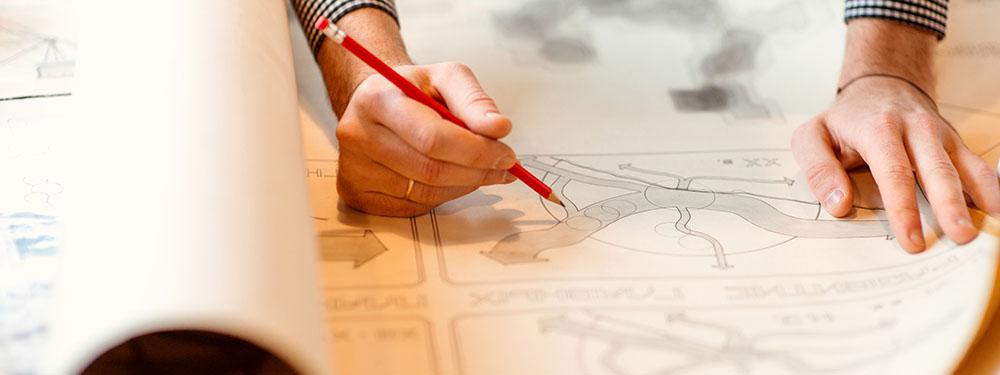 Photo des mains de d'un homme en train de travailler sur un plan d'urbanisme
