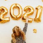 Photo d'une petites fille en train d'installer des ballons 2021 pour la nouvelle année