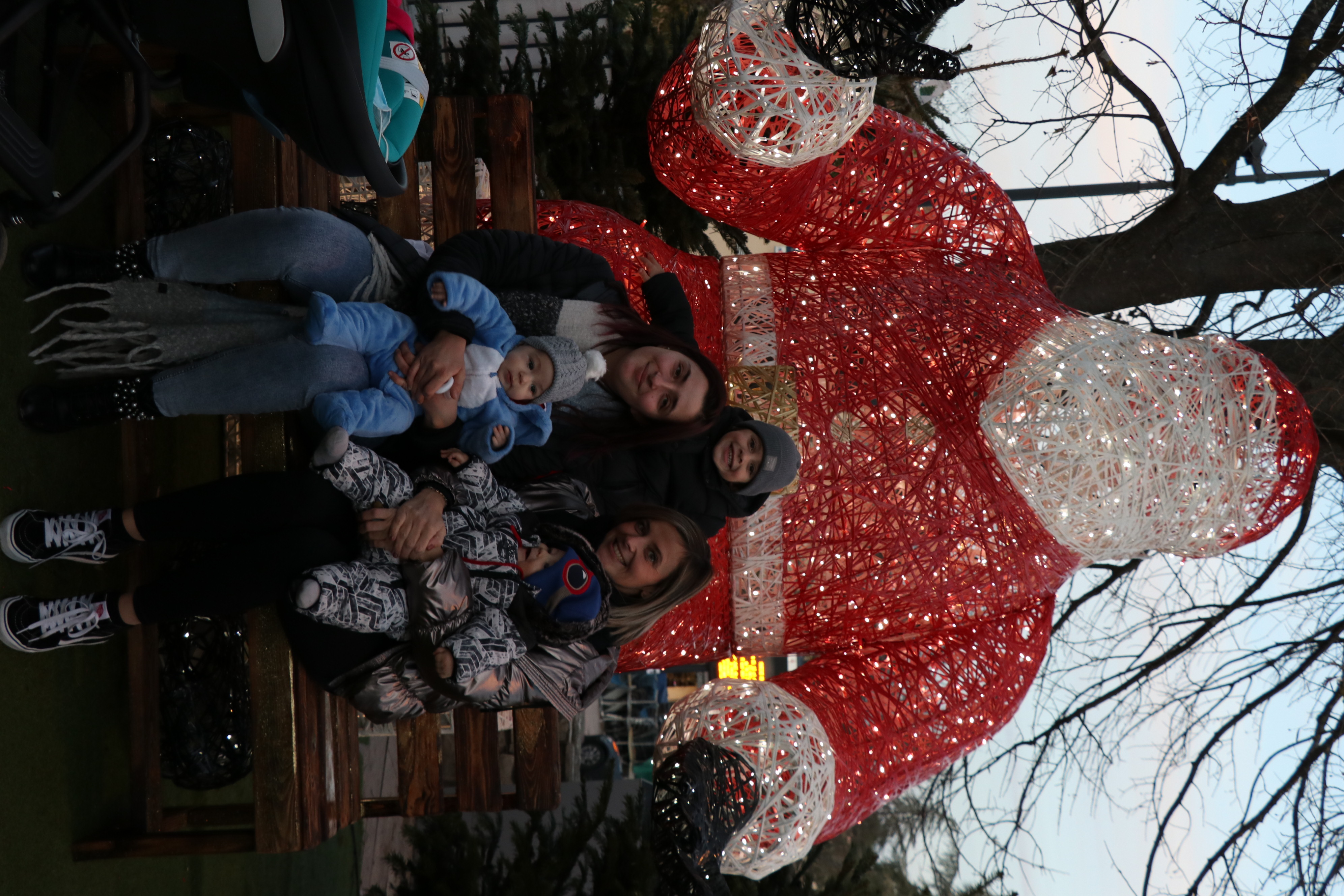 Photo de familles venelloises en train de poser devant le Père Noël géant