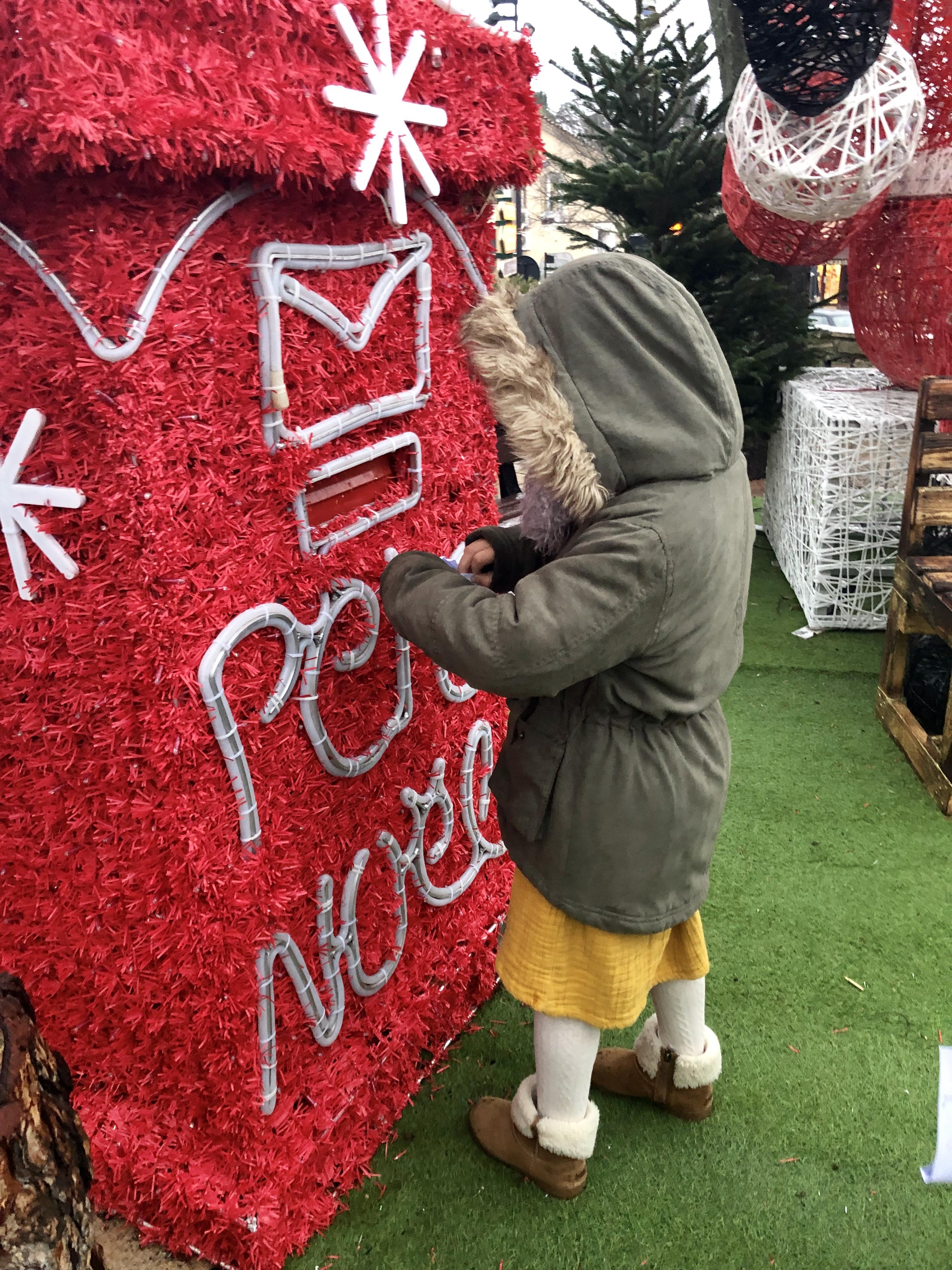 Photo d'une petite fille en train de mettre sa lettre dans la boite aux lettres du Père Noël